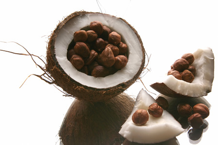 cobnut: hazelnuts in a split coconut on white background