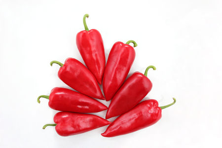 bell peper: seven bright red sweet peppers on a white background