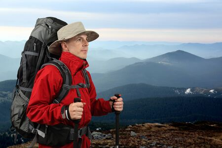 red mountain: the equipped with traveler in a red jacket with Hiking poles looks into the distance