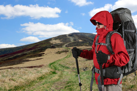 sleeping pad: the equipped with traveler in a red jacket stands on the hillside
