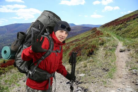 sleeping pad: the happy traveler equipped with a red jacket on the hillside raised in greeting hand