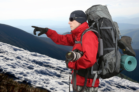 sleeping pad: traveler in red jacket with backpack and camera in hand points into the distance hand being on the hillside