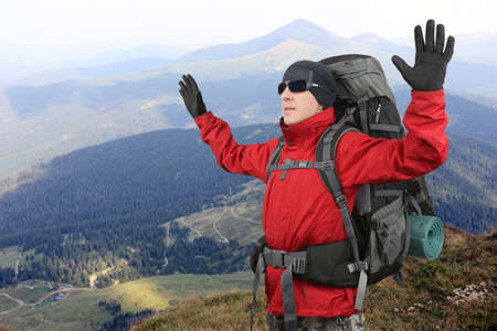 lifted hands: the tourist in red jacket on the elephant mountain with the hands lifted upwards