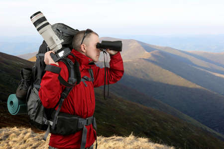 sleeping pad: the equipped with the traveler photographer in the red jacket on the slope of the mountains looking through binoculars Stock Photo
