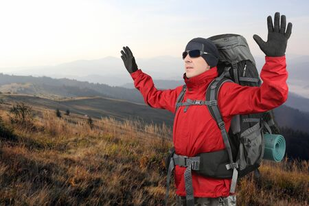 hands lifted: the tourist in red jacket on the elephant mountain with the hands lifted upwards