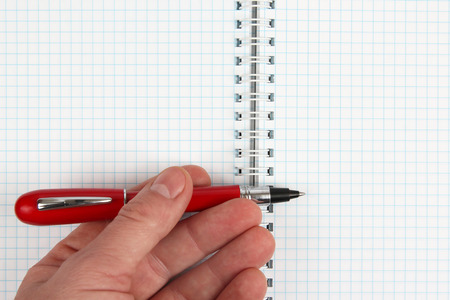 red pen: the hand with red pen over an open notebook
