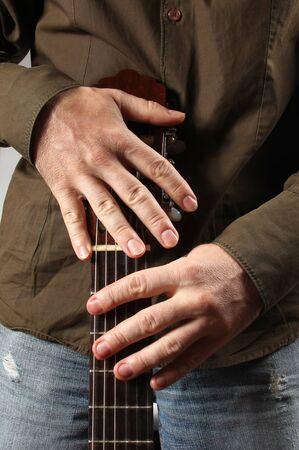 artists model: the musician is holding an acoustic guitar with two hands close up Stock Photo