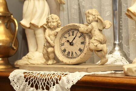 antique clock with two figures of angels