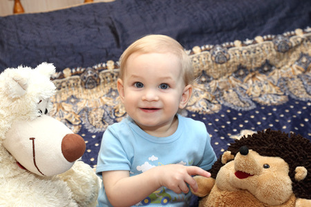 plush toys: the one-year-old blond girl sitting next to plush toys