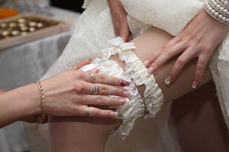 nude bride: the bridesmaid helps to wear a wedding garter Stock Photo