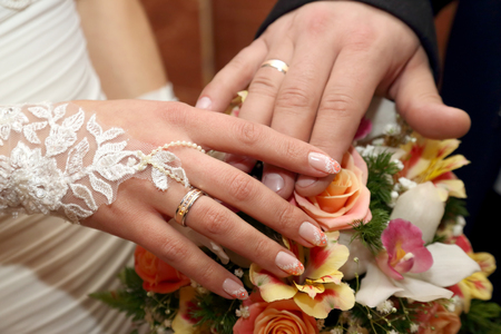 fingers put together: hands of the groom and the bride on background of wedding bouquet Stock Photo