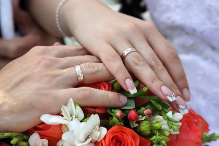 Hände des Bräutigams und der Braut auf Hintergrund des Hochzeitsblumenstraußes