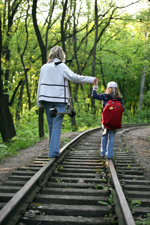 ways to go: young girl with a small child walking on railway tracks