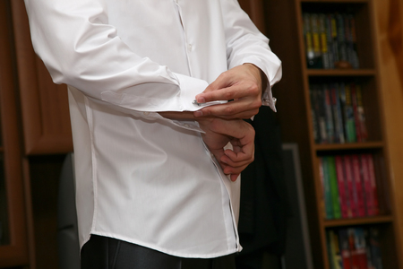 cufflink: the groom wears cufflinks on a white shirt