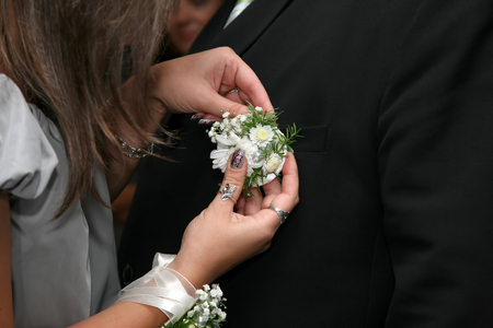 cufflink: the bridesmaid helps to wear the groom wedding flower on suit