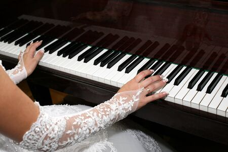 piano closeup: bride plays the piano closeup Stock Photo