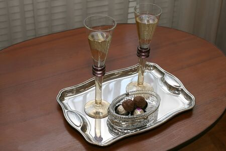 two glasses with champagne and chocolates on a silver tray