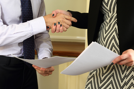 treaty: business people shake hands after signing treaty papers Stock Photo
