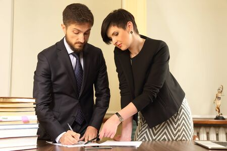advocate symbol: business partners in the office to discuss the documents