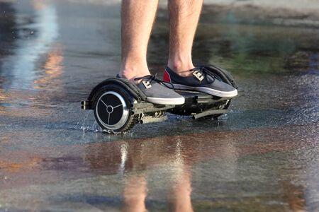 segway: feet ride of a man on a segway on the wet asphalt