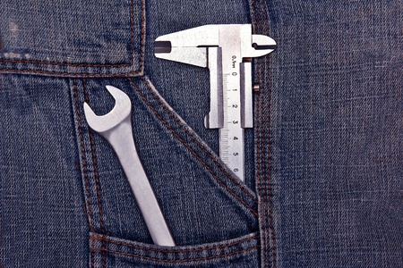 micrometer: tools spanner and micrometer in jeans pocket Stock Photo