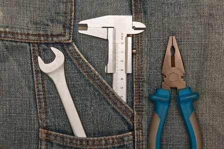micrometer: tools pliers, spanner and micrometer in jeans pocket Stock Photo