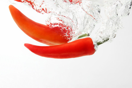 two red hot chili pepper falling into water Stock Photo