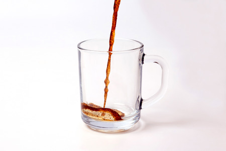 black coffee is poured in a transparent mug on a white background