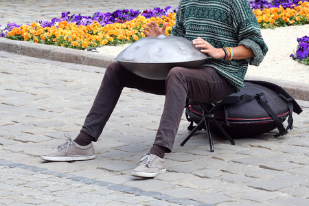 the man on the street plays a percussion instrument hang