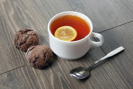 teaspoon: white cup of tea with lemon, teaspoon and cookies on a wooden table Stock Photo