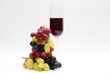 glass with red wine with grapes on a light background Stock Photo