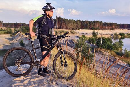 the cyclist with the bike on a sand quarry with binoculars Stock Photo