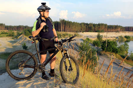 sand quarry: the cyclist with the bike on a sand quarry with binoculars in hand
