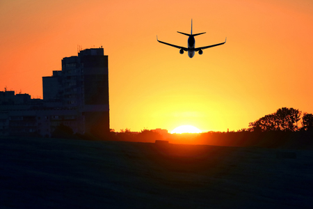 passenger plane flies at sunset on the background of high-rise buildings