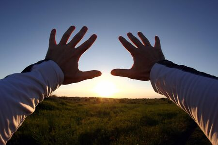 the firmament: Lifted up hands in the background of the sunset