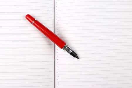 Pluma roja acostado en un cuaderno abierto Foto de archivo
