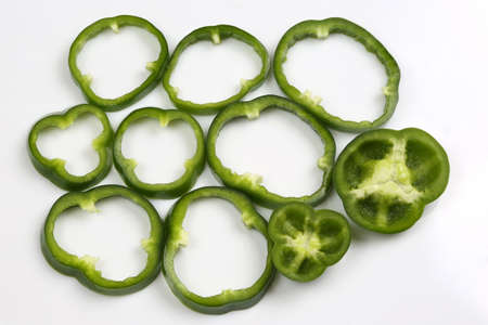 cut into pieces green peppers on white background Stock Photo
