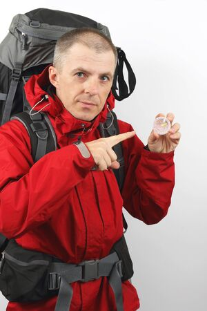 hiker with backpack holding a compass
