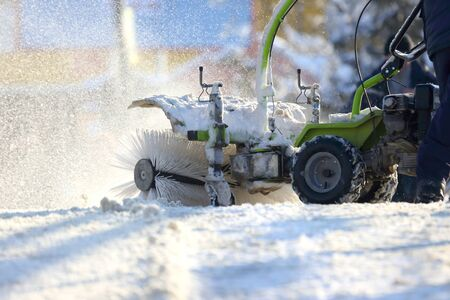 man cleaning the street from snow manual tractor special