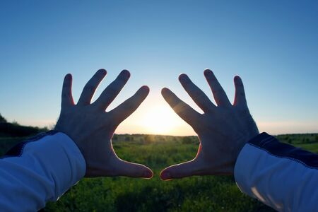 lifted up hands in the background of the sunset