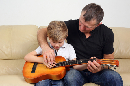 father teaches his son to play the guitar