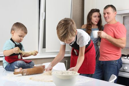 parents see their young sons, who knead the dough on the kitchen table Banque d'images