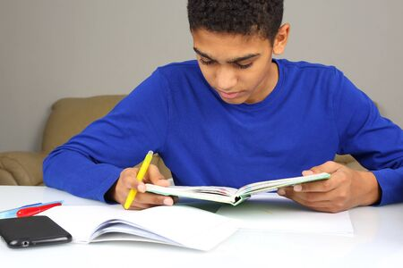 black teen in a blue jacket reading a book Stock Photo