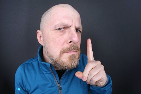 strict bearded man with a pointing finger on gray background