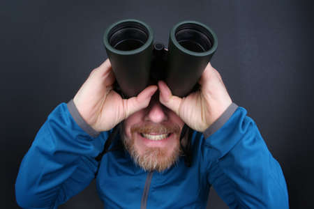 the bearded man looks up through binoculars on grey background