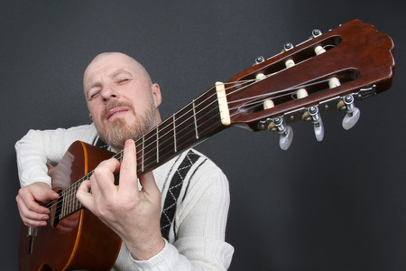 bearded bald man plays classical guitar