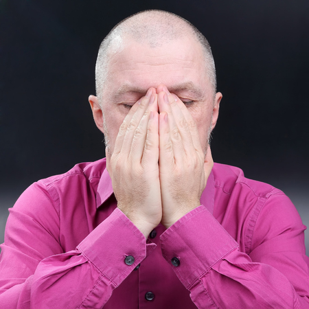 the man closed his face with his hands  Stock Photo