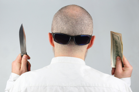 man stands with his back with money and a knife in his hands  Stock Photo