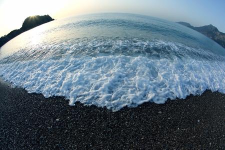Foam wave on the beach at dawn
