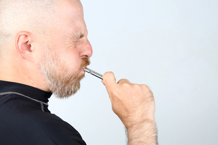 Bearded man in a black jacket blowing a whistle Stock Photo